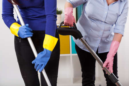 Women wearing protective gloves during cleaning floor