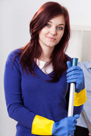 Young woman wearing protective gloves and cleaning