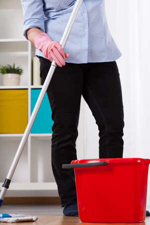 helpers: Woman holding mop during wiping the floor