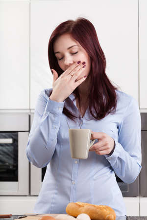 oversleep: Sleepy woman drinking coffee in the morning