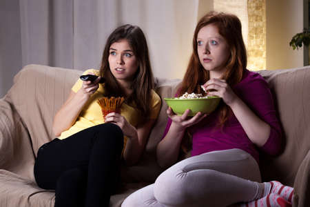 Young girls watching scary movie and eating popcorn photo