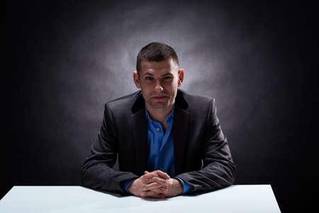 powerful man: An elegant businessman sitting in a dark room by a white desk
