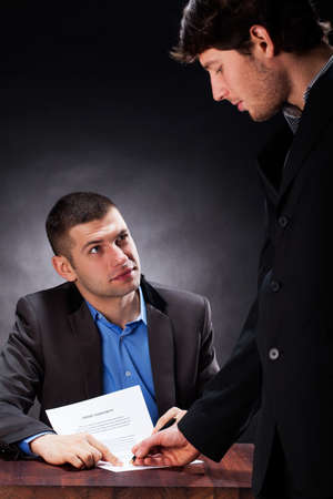 A man signing a credit agreement with a lawyer photo
