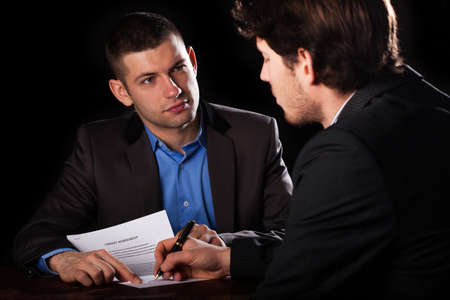 A client signing a loan agreement with his lawyer Stock Photo