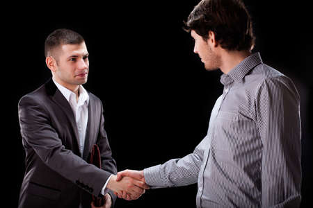professionalist: Two young businessmen shaking hands in agreement
