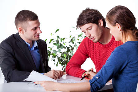 A man and a woman signing mortgage papers at advisory service Stock Photo