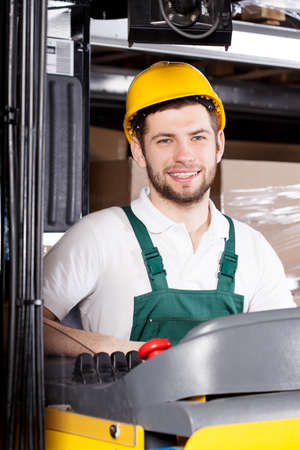 warehouseman: Happy male forklift driver in yellow safety helmet