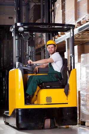 倉庫内の黄色のフォーク リフトの男性労働者の笑みを浮かべてください。 写真素材