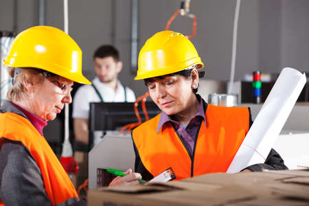 Two female workers in yellow safety helmets in factory