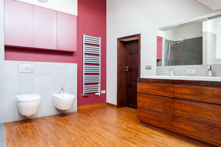 Bathroom with pink wall and wooden furniture photo