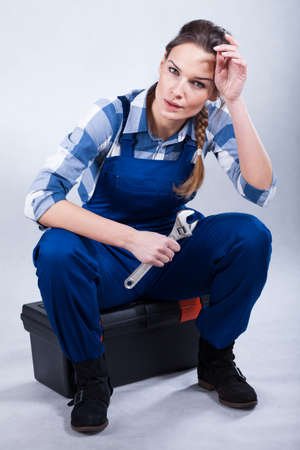 Woman holding a wrench and sitting on her toolbox photo