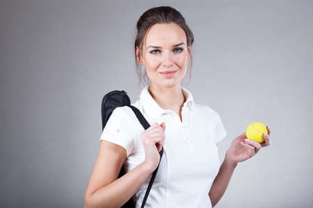 Woman holding a tennis racket in case and a tennis ball photo