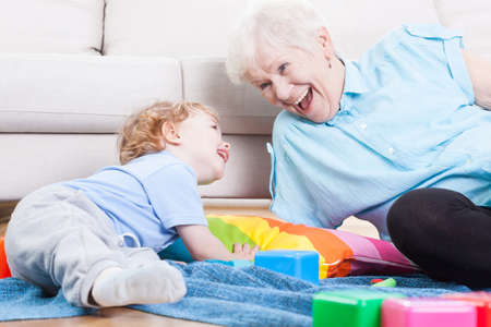 cheerfully: Grandmother cheerfully playing with her grandson indoors