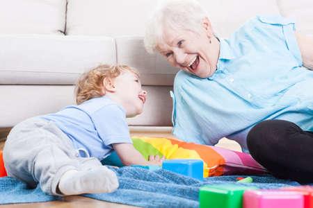 Grootmoeder vrolijk spelen met haar kleinzoon binnenshuis
