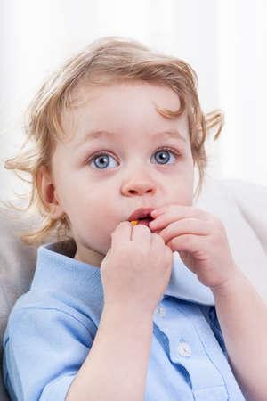 blonde yeux bleus: Mignon littel garçon aux yeux bleus manger