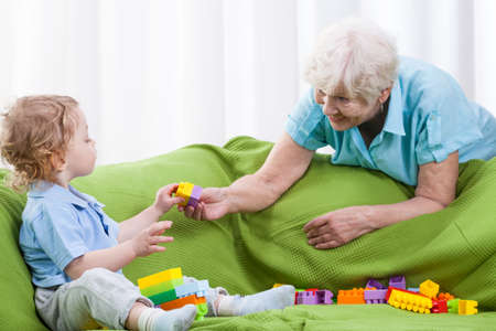 abuela: Abuela que juega alegremente con su nieto en el interior Foto de archivo