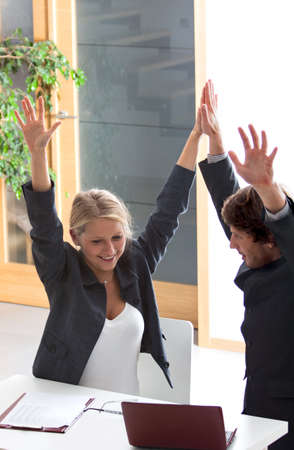business challenge: Joyful man and woman in the office after completing a business challenge
