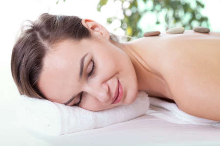 Smiling woman lying and relaxing at spa salon photo