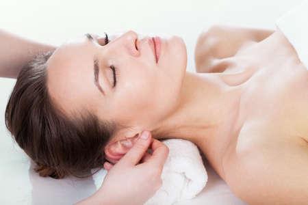 Mujer que disfruta de masaje de la oreja en el salón de belleza