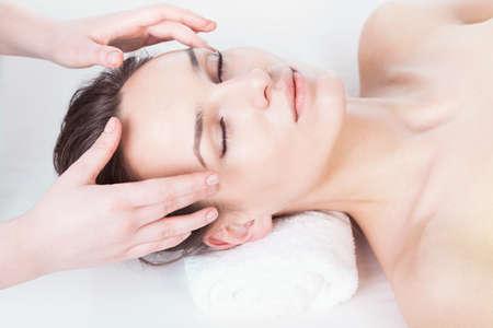 natural therapy: Young woman having head massage at spa salon Stock Photo