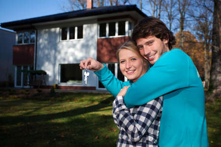 buying a house: Happy couple in front of the new house  Stock Photo