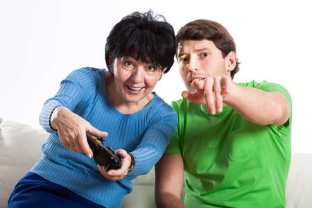 Modern elderly woman playing on console with grandson photo