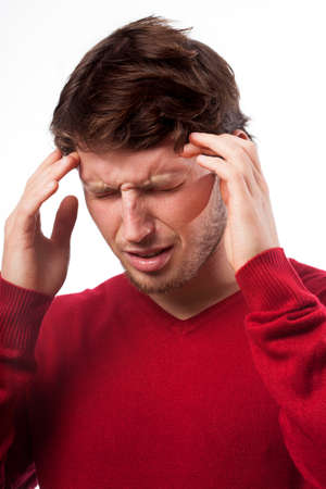 throe: Young man suffering from headache on isolated background