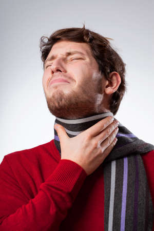 throe: Young man suffering from sore throat, vertical