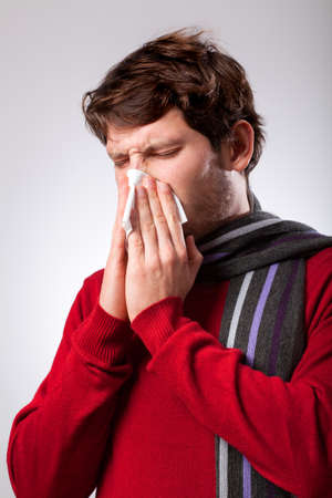 throe: Ailing young man suffering from running nose Stock Photo