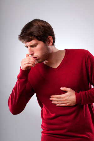 tos: Hombre joven que sufre de tos fuerte, vertical Foto de archivo