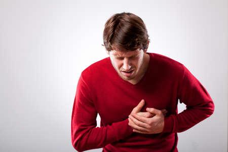 dolor de pecho: Hombre joven con un fuerte dolor en el pecho, horizontal