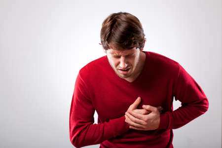 Young man with strong chest pain, horizontal photo