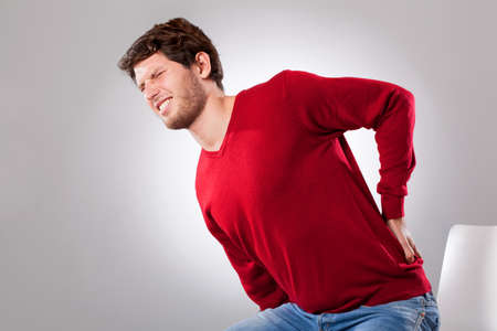 throe: Young man suffering from strong backache, horizontal