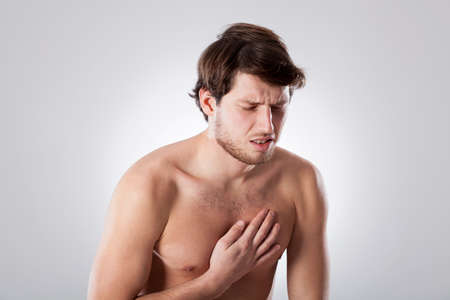 throe: Young man suffering from chest pain, horizontal Stock Photo