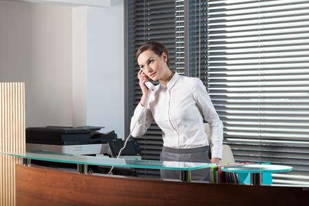 recepcionista: Secretaria hermosa hablando por teléfono en la oficina Foto de archivo