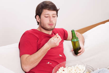 lazybones: Lazy guy eating popcorn and drinking beer Stock Photo