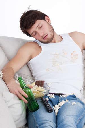 Sleeping male couch potato among junk food  Stock Photo