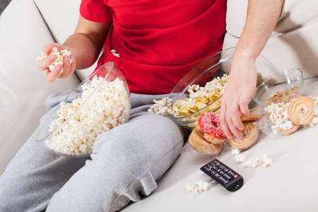 couches: Couch potato watching tv and eating junk food Stock Photo