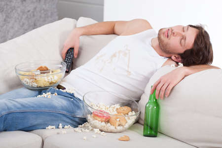 laze: Alcoholic sleeping on couch among beer and sweets Stock Photo