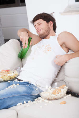 lazybones: Lazy man sitting on couch and watching tv