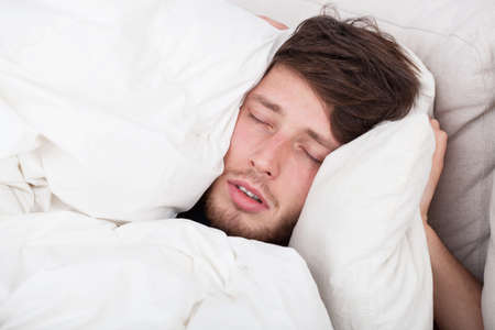 oversleep: Handsome man during sleeping in bed, horizontal