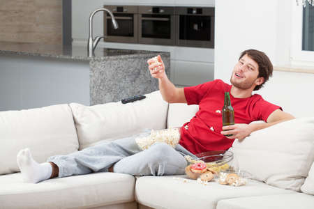 Drinking man during match time sitting on couch photo