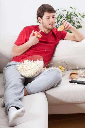 lazybones: Couch potato eating junk food during watching tv