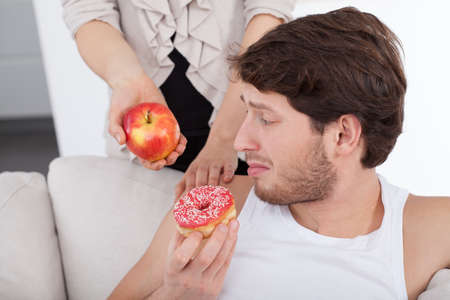 lazybones: Young man choosing donut instead of apple