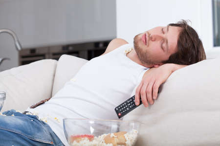 Tired man sleeping on couch in front of tv Stock Photo