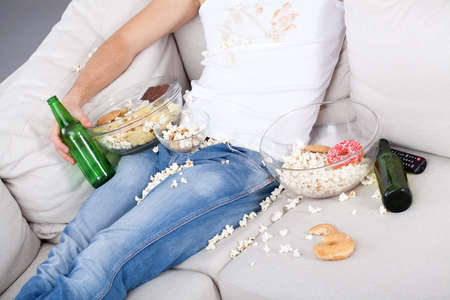 lazybones: Man addicted to alcohol sitting on couch