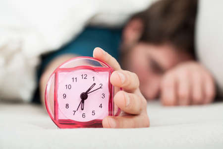 oversleep: Oversleeping man turning off alarm clock, horizontal