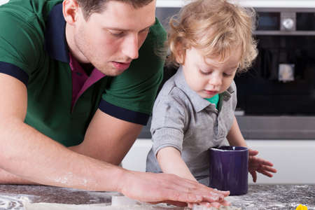 Handsome father cooking with his little son photo