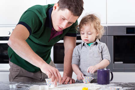 Handsome father baking cookies with little son