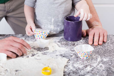 Dad and son baking sweet cookies in kitchen photo
